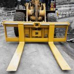 Heavy duty wheel loader pallet forks painted grey.  manufactured by Tysea mfg and installed on a yellow wheel loader